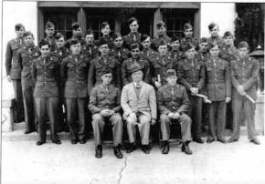 Graduation photo of the 26th QMC War Dog Platoon. The civilian in the front row is their German dog trainer.
